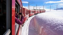 Europe, Switzerland Alps , Poschiavo February 2021 - Live Shot From The Window  Of The  Bernina Express, Red Train  Pass In Ospizio Bernina Station -  White Lake ( Lago Bianco ) Frozen