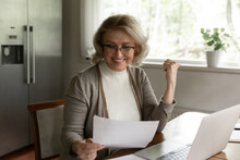 Happy Adult Retiree Woman Reading Bank Document, Checking Account Balance, Smiling At Investment Income, Savings Or Insurance Balance, Getting Good News. Female Pensioner Doing Paper Work At Home