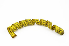 The Yellow Measuring Tape Is Isolated On A White Background. Measurement Of Length And Circumference. The Concept Of Losing Weight And Getting Fat. Top View.