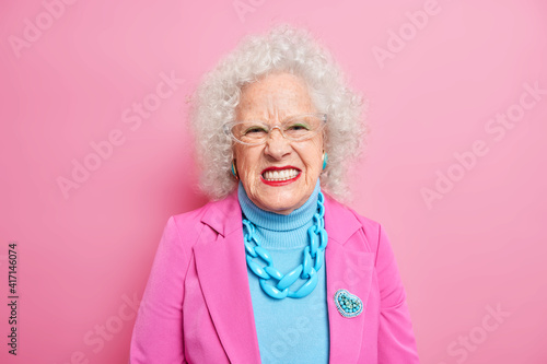 Fotografiet Portrait of angry curly haired senior woman squints face and looks unhappily at