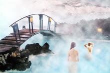 Le Lagon Bleu Le Soir, Reykjavik, Islande. Soins Par Géothermie. Femmes Nues Vues De Dos En Train De Se Baigner Dans Le Spa Naturelement Chaud