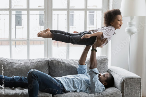 Fototapeta Happy father and little son doing together funny exercises at home. Dad resting on couch, lifting up, holding boy in air, play active game. Excited kid making airplane or boat. Family activity concept obraz