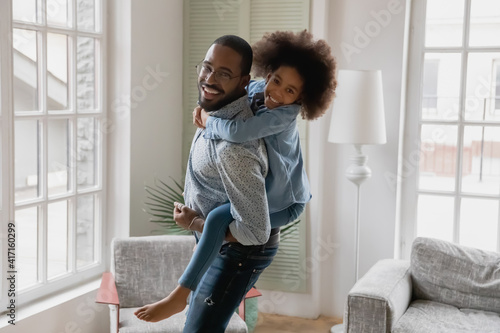 Fototapeta Happy active dad piggybacking kid, carrying girl on his back in living room. Black father and cute daughter girl playing together, enjoying activity at home, smiling, laughing. Family concept obraz