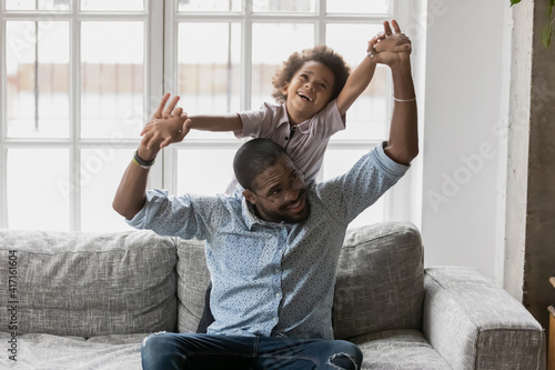 Fototapeta Happy African American father and little son playing active games. Dad and kid enjoying leisure time and home activity. Daddy piggybacking excited laughing boy on couch. Family having fun concept obraz