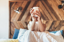 """Lazy Female Lying Down Under The White Blanket On The Linen Bed And Holding The Fresh Coffee Cup In The Early Morning. Lazy Day Off And """"coffee In Bed""""concept Image."""