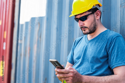 Fotografia Young confident Caucasian man engineer using smartphone and wearing yellow safety helmet and check for control loading containers box from Cargo freight ship for import and export, transport
