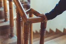 Support, Help And People Concept- Close Up Of A Man's Hand Holding To A Wooden Railing While Climbing A Staircase.