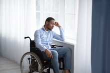 Unhappy Black Handicapped Guy In Wheelchair Looking Out Window, Feeling Sad And Desperate At Home, Copy Space