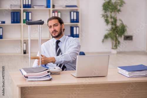 Canvas Print Young leg injured male employee working in the office