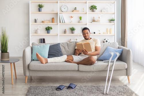 Valokuvatapetti Millennial black guy with plastered leg sitting on sofa, reading book at home, p