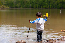 An Active Little Preschooler Boy Is Playing In Shallow Water In The Small Lake At The Catoctin Mountains. His Pants Are Soaked Up Wet But Still Playing In The Mud With Wooden Stick And Toy Shovel.