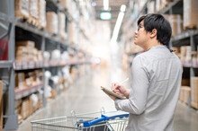 Asian Man Worker Doing Stocktaking Of Product In Cardboard Box On Shelves In Warehouse By Using Digital Tablet And Pen. Physical Inventory Count Concept