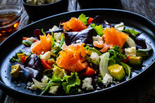Salmon Salad - Smoked Salmon With Feta Cheese, Avocado And Mix Of Vegetables On Wooden Table