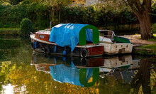 Close Up Autumn Image Of Two River Boats Tied To The Side Of River Yeo In Norwich. Both Are Old And Rustic, One Is Covered With Blue Tarp And Has Old Car Tires Hanging On The Side As Dock Bumpers.