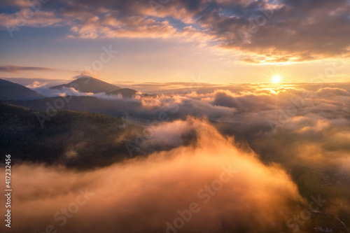 Fototapeta Mountains in clouds at sunrise in summer. Aerial view of mountain peak in fog. Beautiful landscape with high rocks, forest, sky. Top view from drone of mountain valley in low clouds. Foggy hills obraz