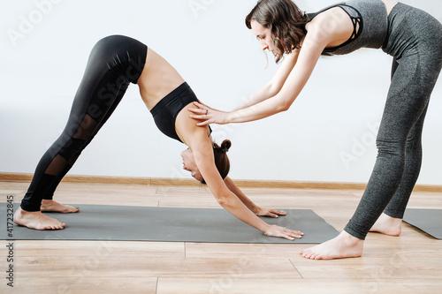 Fotografija Practicing yoga young woman, doing downward facing dog asana with the help of an instructor
