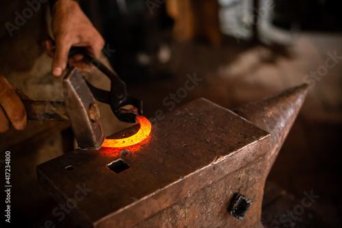 Billede på lærred The blacksmith forging the molten metal on anvil in smithy