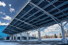 A Modern Solar Carport For Public Vehicle Parking Is Outfitted With Solar Panels Producing Renewable Energy.