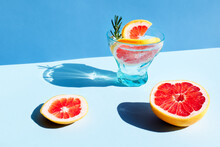 Summer Cocktail With Grapefruit And Rosemary And Juicy Slices Citrus Fruits. Fresh Healthy Grapefruit Beverage On Sunlight With Hard Shadows. Minimal Food Creative Concept On Blue Pastel Background.