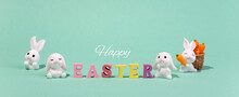 Holiday Banner Happy Easter Wooden Words With Decorative Easter Bunnies On A Turquoise Background.