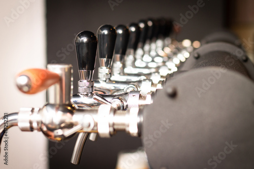 Fotografie, Obraz Partially blurred silvery bar beer taps in pub