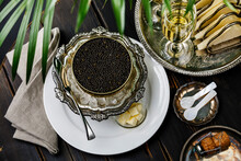 Black Caviar In Can On Ice In Silver Bowl And Champagne On Black Wooden Background Close-up
