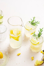 2 Glasses And A Jug Of Lemonade Garnished With Lemon Zest And Slices And Rosemary Branches, Placed On A White Background With Space For Text.