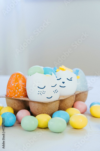 Cute Easter eggs with funny faces full of sweet candies. Easter and spring celebration concept