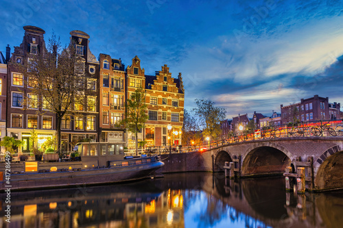 Obraz na plátně Amsterdam Netherlands, night city skyline of Dutch house at canal waterfront