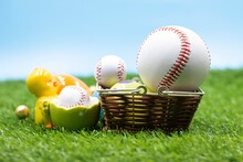 Baseball With Easter Eggs Are On Green Grass For Easter Holiday