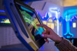 Woman hand using touchscreen display of floor standing tablet kiosk with city map in dark room of museum or exhibition with sci-fi interior: close up side view. Navigation, journey, technology concept