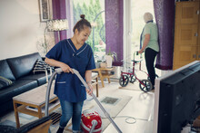 Housekeeper Vacuuming While Senior Woman Looking Out Of Window