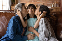 Portrait Of Happy Little Latino 7s Girl Child Kissed By Young Mom And Senior Grandmother, Relax Together At Home. Loving Mother And Mature Grandparent Congratulate Excited Small Kid. Family Concept.