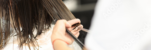 Foto Hairdresser holds client's wet hair and cuts it
