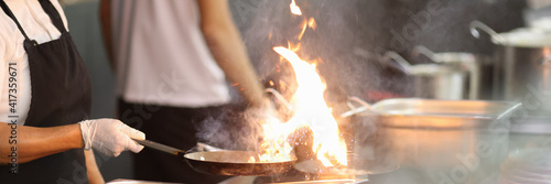 Vászonkép Cook in kitchen holds frying pan in which fire is burning