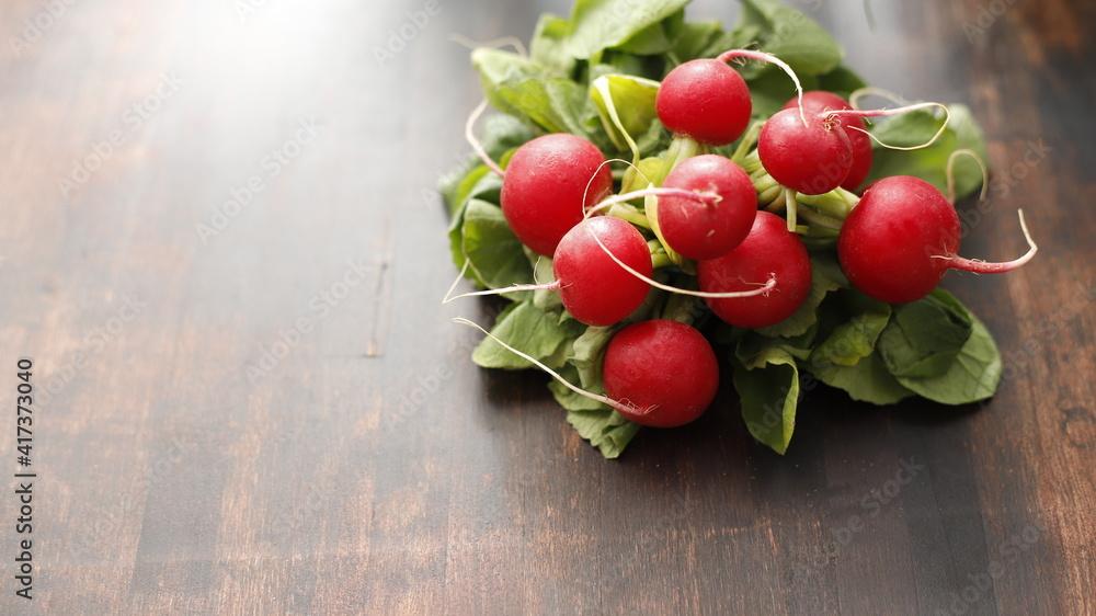 Fototapeta Rzodkiewka w pęczku na stole drewnianym brązowym