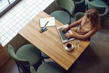 Busy Woman Sitting At Table And Using Laptop