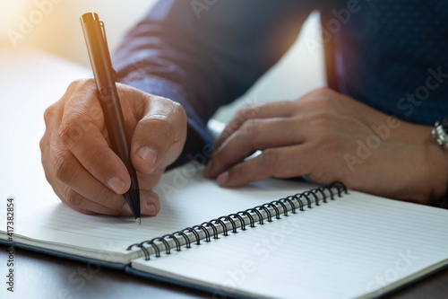 Obraz Close-up of man hand using writing pen memo on notebook paper or letter, diary on table desk office. Workplace for student, writer with copy space. business working and learning education concept. - fototapety do salonu
