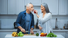 Happy Asian Woman Feeding Husband With Bell Pepper While Preparing Breakfast In Kitchen