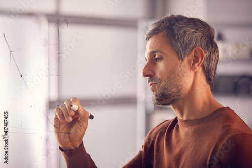 Photo Brainstorming Businessman Or Mathematician Drawing Graph Calculation On Glass Sc