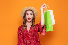 Young Shocked Woman In Red Summer Dress And Straw Hat Holding Shopping Packages In Her Hands Isolated On Orange Background In Studio. Clearance Sale Concept