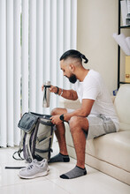 Fit Handsome Man Packing Backpack When Sitting On Sofa In Living Room
