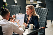 Pretty Smiling Young Businesswoman Showing Chart To Colleague When They Are Discussing Business Activity Of Company And Subdivisions At Meeting