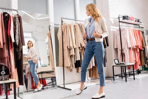 Obraz Smiling woman in jacket looking at mirror in showroom - fototapety do salonu