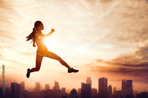 Fototapeta Woman wear sportswear while jumps with cityscape obraz