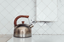 Old Kettle In Kitchen In Front Of White Tiles