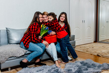 Mother's Day. Daughters Give Flowers To Their Mother. Three Daughters Embraces Mother, Greeting Birthday. Happy Family Sitting On The Couch At Home