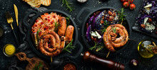Traditional German Dish. Grilled Sausages, Cabbage, Spices And Vegetables. Top View. On A Black Stone Background.