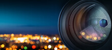 He Camera Lens On The Background Of The Fiery City Lights. Concept On The Topic Of News, Media, Information. Camera Lens Background.