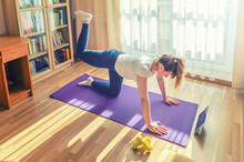 Young Woman Doing Workout Sports At Home, Straight-leg Donkey Kick On All Fours On Floor Mat Pushing Right Foot Out Up And Keeping Leg Bent, Watching Online Tutorials Video On Tablet Screen In Room